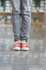 woman in sneakers standing at high heels