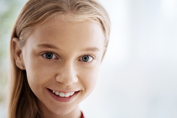 Cute girl. Pleased young emotional girl being in a good mood and smiling cheerfully while being alone