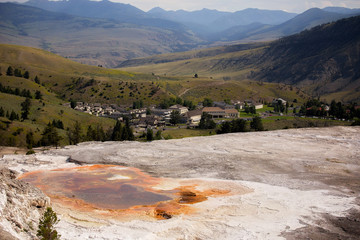 Orange, white and grey sulfuric springs overlooking mountains and town of Mammoth Hot Springs in a summertime Wyoming landscape