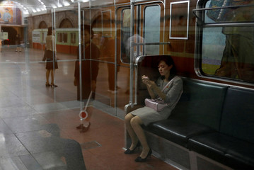 A woman sits in a train at a subway station in Pyongyang