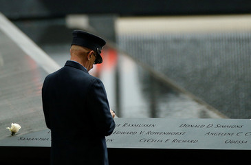 A guest looks at names on the National 9/11 Memorial during ceremonies marking the 17th anniversary of the September 11, 2001 attacks on the World Trade Center, at the National 9/11 Memorial and Museum in New York
