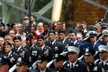 Uniformed guests salute during the ceremonies marking the 17th anniversary of the September 11, 2001 attacks on the World Trade Center, at the National 9/11 Memorial and Museum in New York