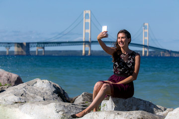 Woman taking selfie photo by landmark bridge and bright blue bay water
