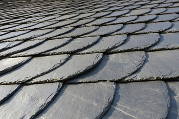 roofing: pattern of gray slate on an antique roof lightend by the sun