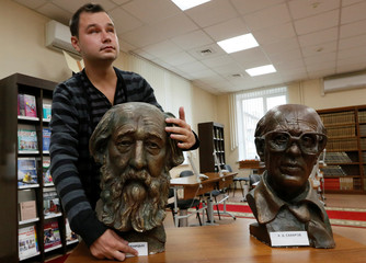 A man with vision impairment feels a bust of dissident author Solzhenitsyn next to a bust of dissident and scientist Sakharov at a specialized library for blind and partially sighted people in Krasnoyarsk