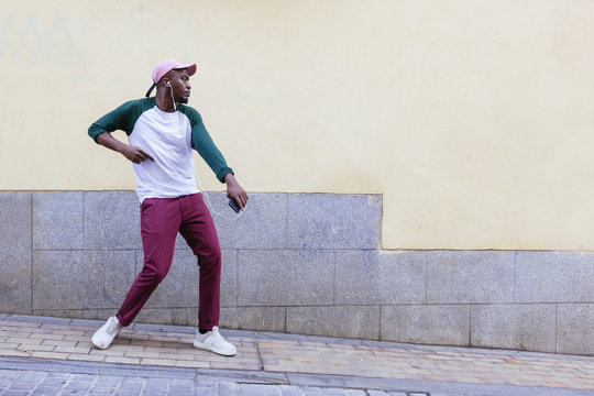African-American male in red pants dancing at street