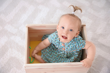 Adorable baby girl playing in wooden cart at home