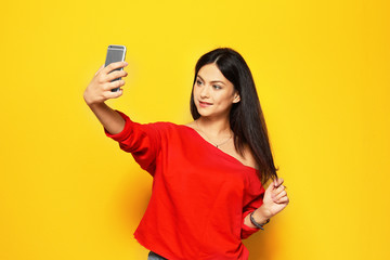 Attractive young woman taking selfie on color background