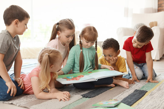 Cute little children reading book together indoors. Learning by playing