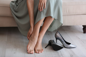 Barefoot tired woman sitting on sofa at home, closeup view