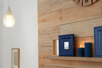 Shelf with burning candles against wooden wall