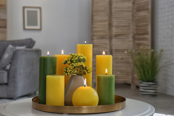 Tray with burning candles on table in living room