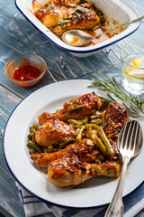 Baked chicken legs with peas, beans and fresh herbs. Chicken drumsticks with tasty sause and greens.