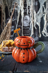 Fun colorful pumpkin mug filled with pumpkin spice drink in Halloween setting