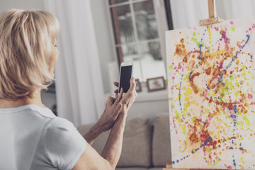 Picture of canvas. Blonde-haired elderly woman feeling motivated while taking picture of her creative colorful canvas