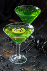 Halloween bright green dessert topped with apple slice with black spiders and spider webs