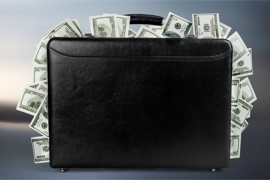 Black suitcase full of banknotes on backgrouund