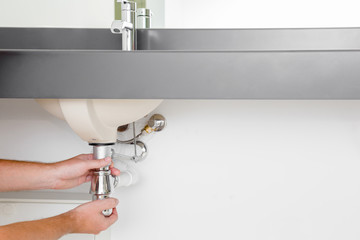 Man's hand checking new metal siphon under the sink. Commercial plumbing company. Empty place for text or logo on white wall background.