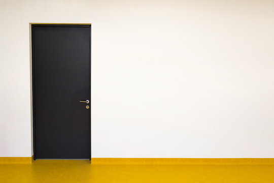 Closed dark door with beige wall and yellow linoleum floor. Empty place for text or objects.
