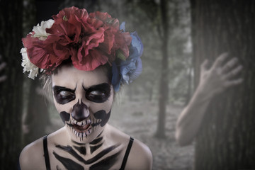 Curly hair girl with sugar skull Catrina Calavera make up and red rose natural flowers headband close up. Day of Dead. Dia de Los Muertos