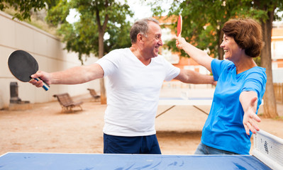 elderly couple enjoys victory at table tennis at outdoor