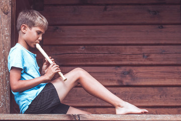 Boy sitting on terrace and playing flute outdoors