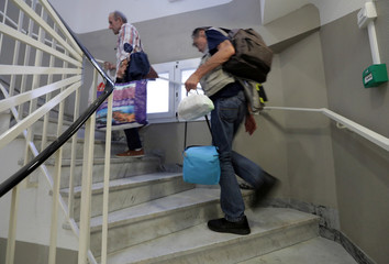 "Homeless men climb stairs to reach their rooms at the ""Abbe Pierre"" night shelter for the homeless in Nice"