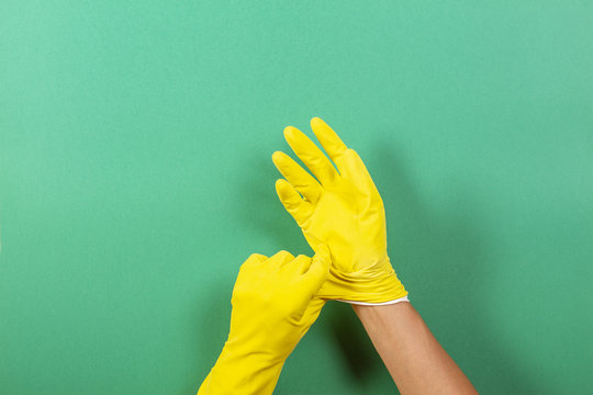 Hands putting on yellow rubber gloves