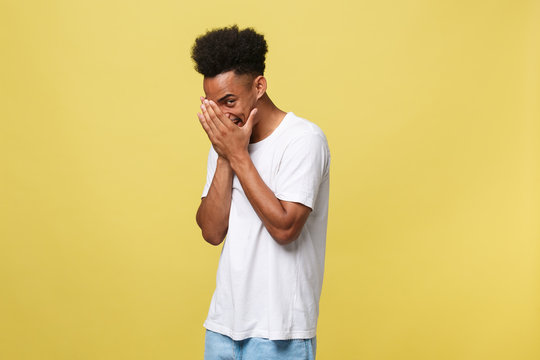 African american man with beard smiling having shy look peeking through fingers, covering face with hands looking confusedly broadly isolated over yellow background
