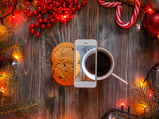 blogging and mobile photography concept. christmas and new year festive decor on wooden background, fairy lights and bead strings surrounding cup of coffee and chocolate chip cookies.