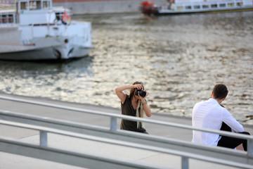 Kobieta fotograf robi zdjęcia parze młodych ludzi w plenerze nad rzeką.