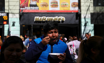 A man eats a free meal at a soup kitchen set up on a street during a demonstration against the government's economic measures in Buenos Aires