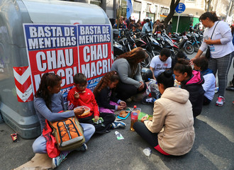 People eat a free meal in soup kitchens set up on a street during a demonstration against the government's economic measures in Buenos Aires