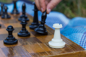 soft focus human hand on black chess classic figure on wooden desk with quadratic marking in game time