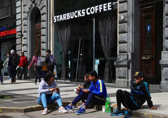People eat a free meal from a soup kitchen set up on a street, as they sit in front of a Starbucks coffee shop, during a demonstration against the government's economic measures in Buenos Aires
