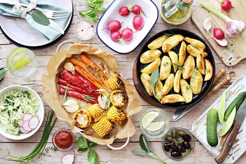 Food grilled vegetables outdoor table family dinner potato wedges roasted corn party picnic. Overhead view, copy space