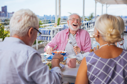 So funny. Happy aged bearded man being in a great mood while listening to his friends jokes