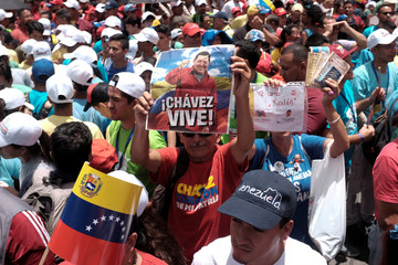 "A man holds a banner with the image of Venezuela's late President Chavez that reads ""Chavez lives!"" during a rally in support of Venezuela's President Maduro in Caracas"
