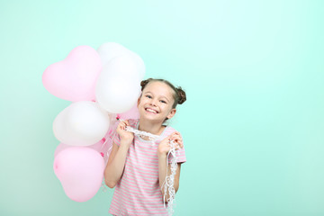 Beautiful young girl with balloons on mint background