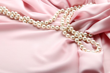 Pearl necklace on pink satin fabric
