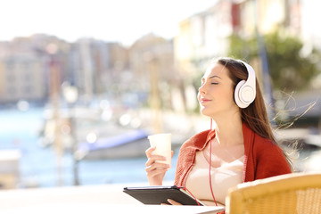 Girl relaxing in a coffee shop listening to music on vacation