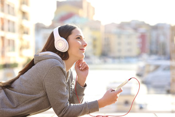 Dreamer girl listening to music on vacation