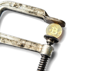 BITCOIN coin being squeezed in vice on white background; concept of cryptocurrency bitcoin  under pressure. Prohibition of cryptocurrencies, regulations, restrictions or security. Isolated. Close up.