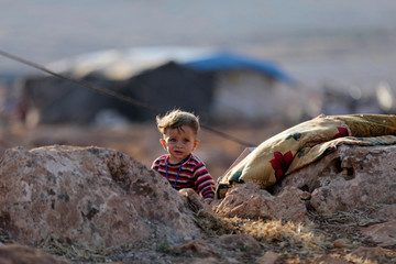 A newly displaced Syrian child walks near a refugee camp in Atimah village, Idlib province