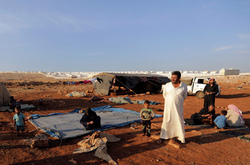 Newly displaced Syrians arrive to a refugee camp in Atimah village, Idlib province