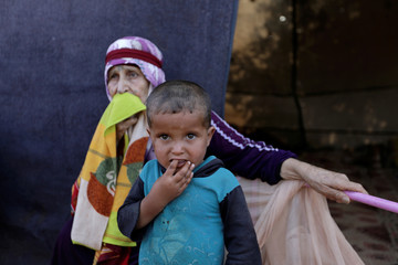 Newly displaced Syrians react after their arrival to a refugee camp in Atimah village, Idlib province