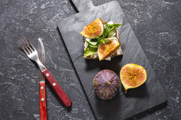 Figs fruit sandwich on a slate plate on a black background