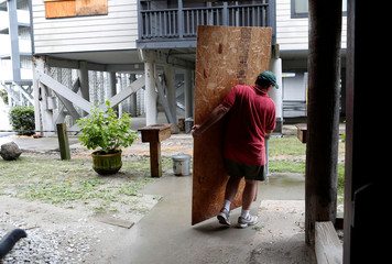 John Muchmore helps carrying hurricane shutters at the Afterdeck condos ahead of the arrival of Hurricane Florence in Garden City Beach