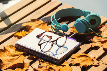 Notebook with glasses, headphones and maple leaves on wooden table. Side view