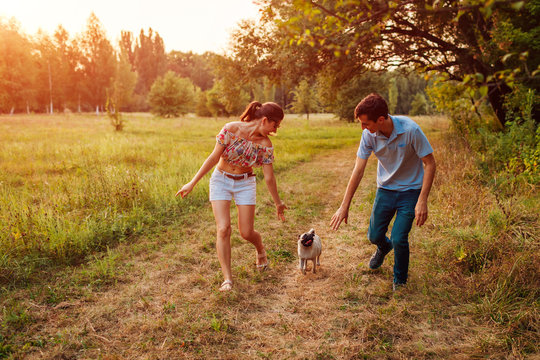 Young couple walking pug dog in autumn forest. Happy puppy running along and having fun playing with masters.